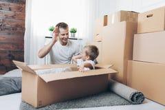 Concepto móvil, padre e hijo moviéndose a un nuevo hogar foto de archivo