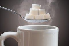Concepto malsano de la consumición Muchos azucaran los cubos sobre la taza caliente de té o de café foto de archivo libre de regalías