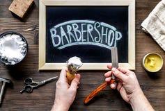 Concepto masculino de la peluquería con las manos de la barbería en la opinión superior del fondo de la tabla Fotografía de archivo libre de regalías