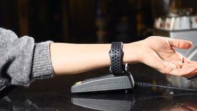 Concepto moderno del pago Tiro del primer del cliente que paga con tecnología de NFC por el reloj elegante a mano sin contacto en metrajes