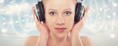 Concepto musical. la mujer disfruta de la música en los wi del fondo del cielo Imagen de archivo libre de regalías