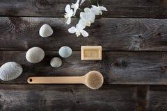 Concepto natural del baño con los guijarros, el cepillo de la parte posterior y las orquídeas blancas Imagenes de archivo