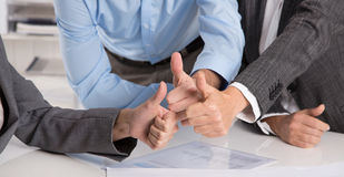 Concepto para el trabajo en equipo acertado: hombres de negocios que hacen los pulgares u Foto de archivo libre de regalías