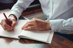 Concepto para hacer el mensaje de la lista en el cuaderno con las manos del hombre de negocios Imagen de archivo