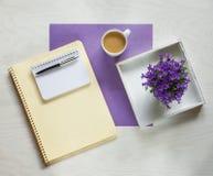 Concepto plano de la endecha con el cojín de escritura, la pluma y las flores violetas hermosas Imagen de archivo