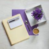 Concepto plano de la endecha con el cojín de escritura, la pluma y las flores violetas hermosas Fotos de archivo