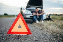 Concepto quebrado del coche, hombre que se sienta en el neumático Foto de archivo