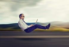 Concepto rápido del Internet Elevar y mantener flotando al hombre de negocios en el camino usando el ordenador portátil Foto de archivo
