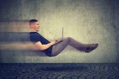 Concepto rápido del Internet Elevar y mantener flotando al hombre de negocios joven en el camino usando el ordenador portátil imágenes de archivo libres de regalías