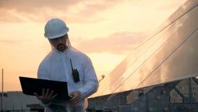 Concepto respetuoso del medio ambiente de la energía El constructor solar masculino está actuando un ordenador portátil mientras  metrajes