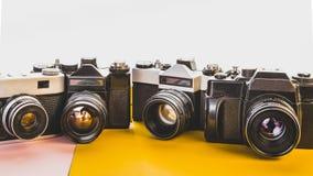 Concepto retro de la tecnología de la creatividad Cámaras de la película del vintage en el fondo amarillo y rosado, Front View Imagenes de archivo
