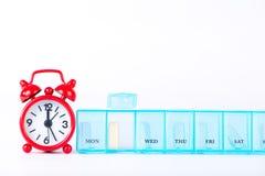 Concepto rojo del tiempo de la medicina de la demostración del despertador y dialy de la caja de la píldora Imagen de archivo libre de regalías
