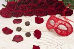 Concepto romántico del carnaval Máscara roja del carnaval, ramo de rosas rojas y chocolates en fondo de madera ligero imágenes de archivo libres de regalías