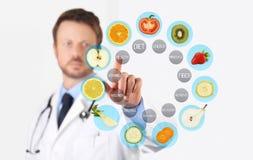 Concepto sano de la comida, mano del doctor del nutricionista que señala la fruta imagenes de archivo