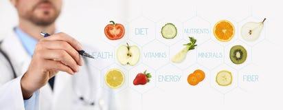 Concepto sano de la comida, mano del doctor del nutricionista que señala la fruta Imagen de archivo libre de regalías