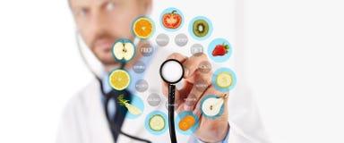 Concepto sano de la comida, mano del doctor del nutricionista que señala las frutas fotografía de archivo