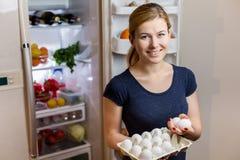 Concepto sano de la consumición Dieta Mujer joven hermosa cerca del refrigerador con los huevos Alimento sano Frutas y verdura ad Fotografía de archivo