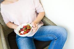 Concepto sano de la consumición El ` s de las mujeres da sostener el cuenco con muesli, el yogur, la fresa y la cereza lifestyle foto de archivo libre de regalías