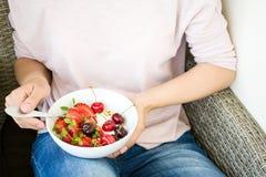 Concepto sano de la consumición El ` s de las mujeres da sostener el cuenco con muesli, el yogur, la fresa y la cereza lifestyle imagenes de archivo