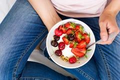 Concepto sano de la consumición El ` s de las mujeres da sostener el cuenco con muesli, el yogur, la fresa y la cereza Visión sup Imagenes de archivo