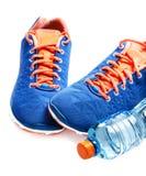 Concepto sano de la forma de vida Zapatos y agua del deporte en backgro gris Foto de archivo libre de regalías