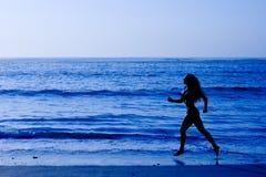 Concepto sano de la vida - mujer que se ejecuta en la playa Imágenes de archivo libres de regalías