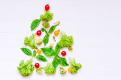 Concepto sano del Año Nuevo - colección de verduras y de greeens orgánicos frescos en la forma de árbol de navidad en el fondo de Imagen de archivo libre de regalías