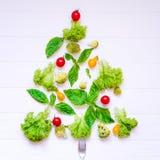 Concepto sano del Año Nuevo - colección de verduras y de greeens orgánicos frescos en la forma de árbol de navidad en el fondo de Imagenes de archivo