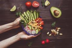 Concepto sano del alimento Manos que sostienen la ensalada sana con el garbanzo y las verduras Comida del vegano Dieta vegetarian fotos de archivo