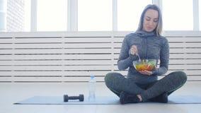 Concepto sano del alimento Mujer feliz que come la ensalada verde sana después de entrenamiento en un interior blanco almacen de video