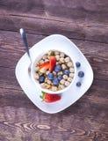 Concepto sano del desayuno con las escamas de la avena y las bayas frescas en r Imagen de archivo