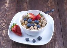 Concepto sano del desayuno con las escamas de la avena y las bayas frescas en r Imagenes de archivo