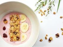 Concepto sano del desayuno con un cuenco de youghurt fresco con el plátano fotografía de archivo
