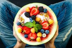 Concepto sano del desayuno del verano, ensalada de fruta en sandía tallada Cuenco de la sandía con el yogur, semillas del chia, b Imagenes de archivo