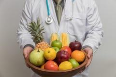 Concepto sano y de la nutrición Doctor que sostiene el cuenco de frutas y verduras frescas imagen de archivo libre de regalías