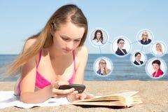 Concepto social de la red - mujer que miente en la playa con p móvil Imagen de archivo libre de regalías