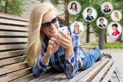 Concepto social de la red - mujer que usa smartphone e iconos con p Foto de archivo libre de regalías