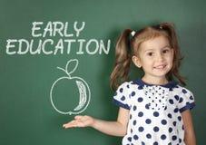 Concepto temprano de la educación, muchacha del niño cerca de la pizarra de la escuela foto de archivo