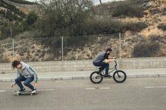 Concepto urbano extremo de los deportes Gente joven con las bicicletas y los monopatines del bmx en la calle fotos de archivo