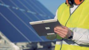Concepto verde de la energía Ciérrese para arriba de una tableta en las manos de un constructor solar del ` s del módulo almacen de video