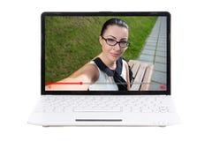 Concepto video del blog - ordenador portátil con el blogger de la mujer joven en la pantalla i Foto de archivo libre de regalías