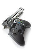 Concepto virtual y de la vida real - regulador del videojuego con la arma de mano real cerca de ella Fotos de archivo libres de regalías