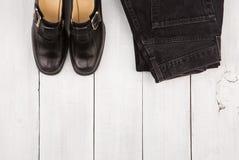 Concepto, zapatos y vaqueros del viaje en el escritorio de madera blanco Fotos de archivo libres de regalías