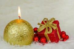 Conceptos de la Feliz Navidad con la vela y el rojo presentes Imagen de archivo libre de regalías