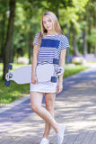 Conceptos de la forma de vida del adolescente Muchacha rubia caucásica sonriente feliz del adolescente que presenta con Longboard Foto de archivo libre de regalías