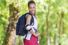 Conceptos de la forma de vida Retrato del adolescente afroamericano positivo feliz Presentación al aire libre en parque Imagenes de archivo