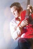 Conceptos de la música Retrato de la ejecución masculina joven del guitarrista Fotos de archivo