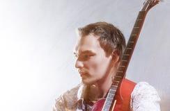 Conceptos de la música Retrato del guitarrista masculino joven contra Gra Foto de archivo libre de regalías