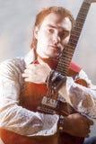 Conceptos de la música Retrato del guitarrista masculino joven que presenta con Fotografía de archivo