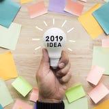 Conceptos 2019 de las ideas de la inspiración con la mano que sostiene la bombilla blanca imagenes de archivo